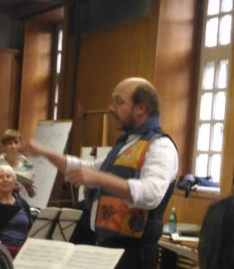 A photo of a choir rehearsal with Christophe Jean-Baptiste